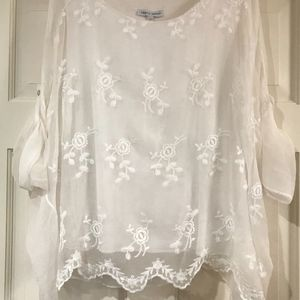 White sheer blouse with floral lace overlay.
